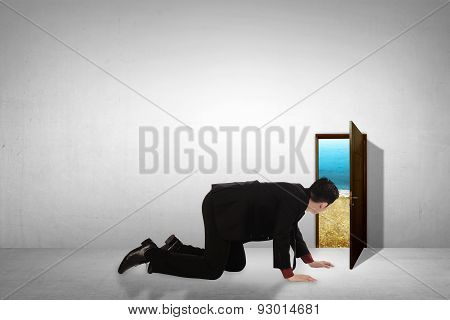 Business Man Take Peek On Small Door Through Beach