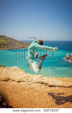 Girl Jumps In The Air At The Coast