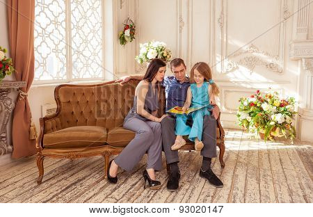 Father and mather reading book to her daughter