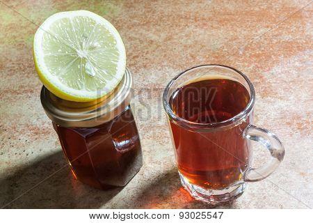 Glass of tea with slice of lemon and bottle of honey