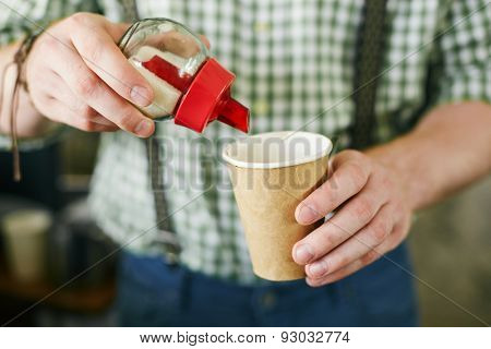 Hands of barista adding sugar in takeout paper cup with coffee