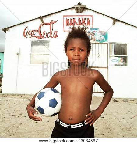 Boy posing with a ball in township, South Africa.