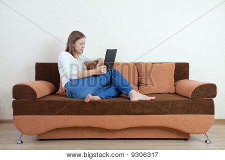 Woman With Laptop On The Sofa