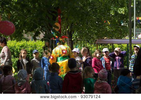 Preschool Teacher Entertain Children In Suits Of Buffoons At The Festival