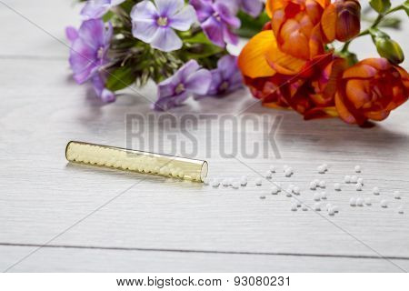 Small Glass Tube With Homeopathy Globules  And Flowers