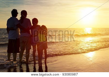 Happy Family Watching The Sunset On The Beach