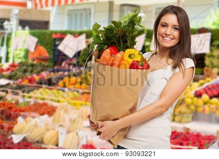 Woman holding a bag in a fruit and vegetable outdoor market
