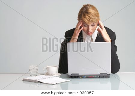 tired businesswoman is sitting behind her laptop with headache poster