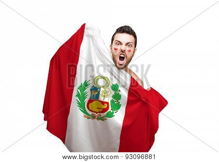 Fan holding the flag of Peru celebrates on white background