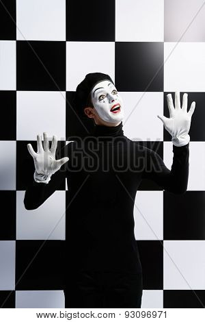 Professional mime artist performing different emotions. Chess board background.