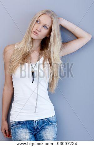 Beautiful nordic type woman posing by wall, having long blonde hair.