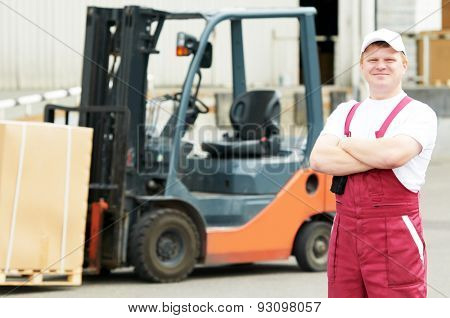 young warehouse worker portrait in uniform in front of modern storehouse forklift machine