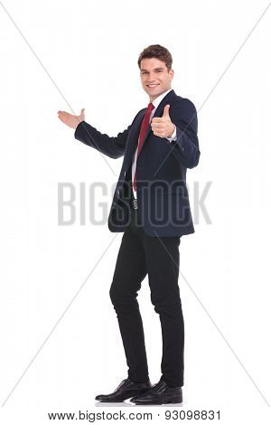 Full body picture of a young handsome business man presenting while showing the thumbs up gesture.