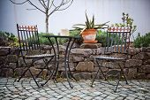 Cast iron garden furniture on a patio with a small table and two chairs standing in the sunshine alongside a walled rock garden with a potted cactus on top of the wall poster