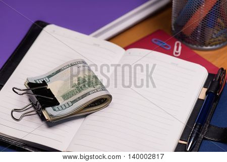 Empty notepad with US dollar banknotes and pen on table