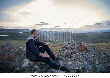 man sits on a background of mountains