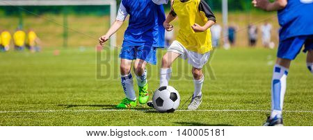 Kids playing football soccer game on sports field. Boys kicking soccer ball. Horizontal sport background