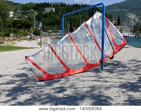 RIVA ITALY - JULY 3 2016: Sail of surfboard hung out to dry at lake Garda people sunbathing on shore