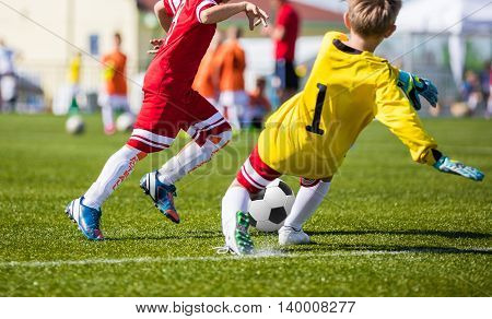 Football soccer game. Players footballers running and playing football match. Forward youth footballer against goalkeeper.