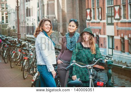 Tourists with bicycles taking a tour along the narrow canals and old houses of Amsterdam