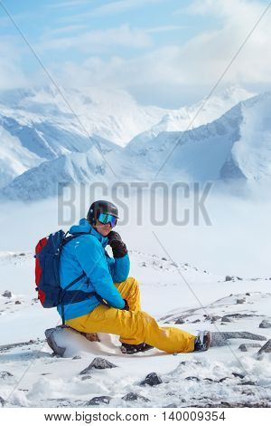 Young adult in a ski helmet and goggles, sitting on the stone. With high snowy mountains in the background