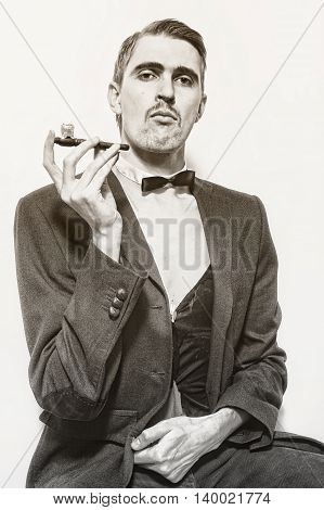 Retro portrait of an adult man smoking a pipe closeup