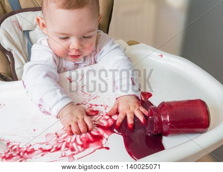 Messy And Dirty Baby Is Eating Snack With Hands.