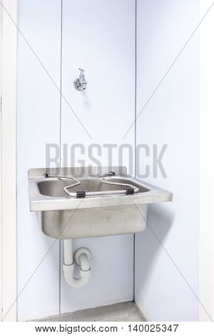 in an public restroom hangs on an wall of an inox sink