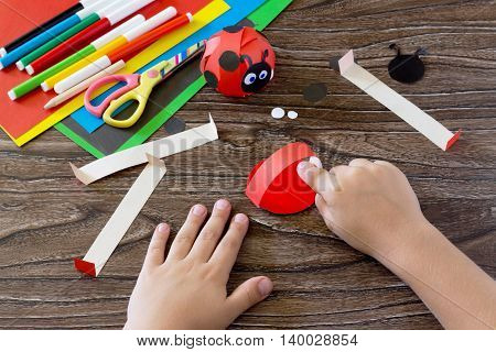 The Child Holds A Piece Of Paper And Glues The Of The Handicrafts. The Child Makes Crafts Out Of Pap