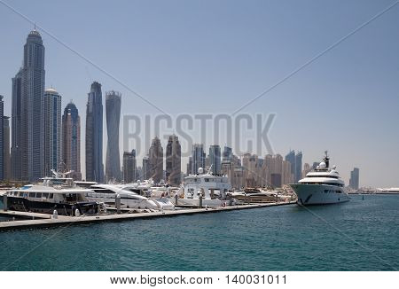 boats in front of towers of district Marina in Dubai