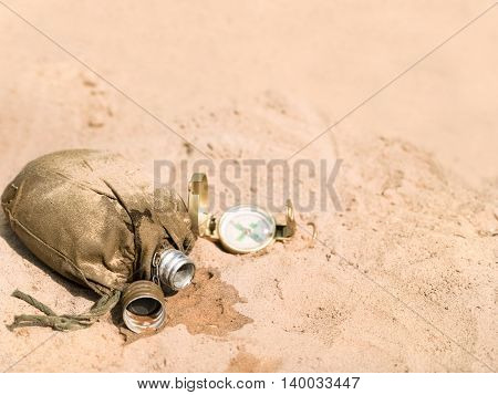 An empty military looking flask laid on the sand next to the compass. Closeup filtered shot concept of the survival