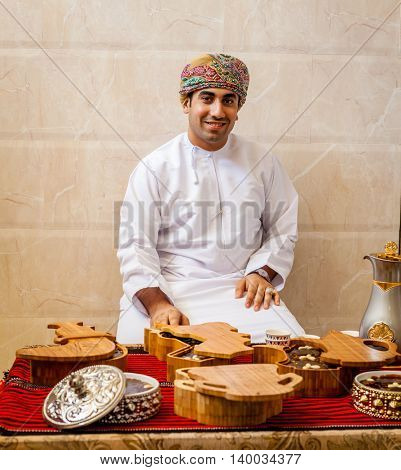 NIZWA, OMAN, MAY 27, 2016: Omani man behind a table with traditional Omani sweets