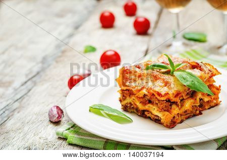 Meat lasagna on a white wood background.