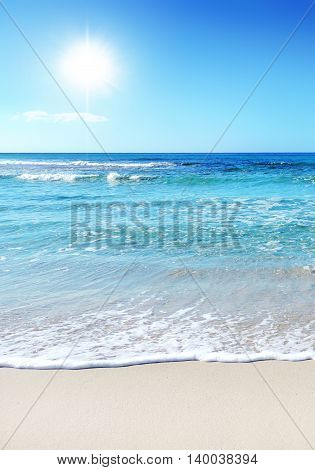 Tropical beach with waves and turquoise water. Sunbeam and gently rolling waves.