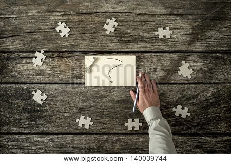 Eight blank puzzle pieces spaced evenly around hand written question mark near human arm holding pen over wooden table.