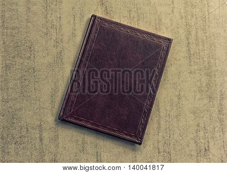 the book is dark purple on a grey grunge background top view. tinted photo retro toned image