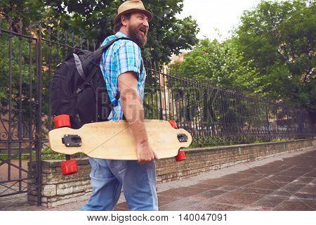 Freaky bearded man walking with longboard in hand