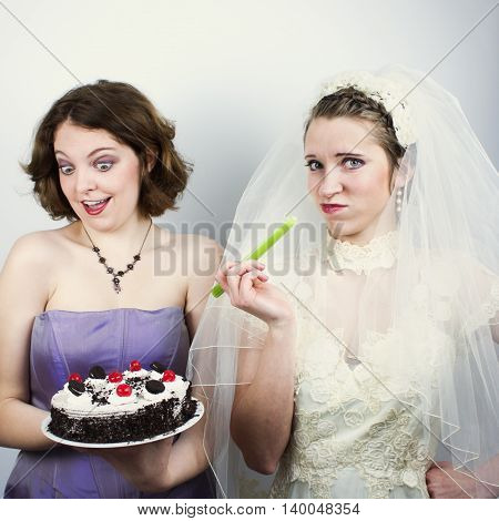 Bride trying to diet and eating celery is tempted by bridesmaid holding up cake.