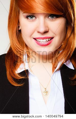 Portrait of beauty redhair smiling business woman or student girl. Studio shot on gray background