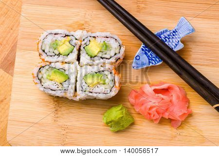 Sushi California rolls appetizer with rice avocado with chopsticks poster