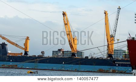 Shipping Port. A large bulk carrier loaded with ship cranes. Ship in cargo port terminal. Container ship being unloaded in the Rotterdam harbor. Trade sea port .