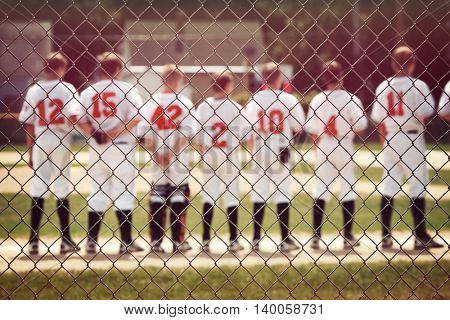 Blurred youth baseball background, children in a row with their hats off at the beginning of a game.