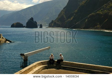 Two old men relaxing near the Atlantic Ocean in Porto Moniz Madeira poster