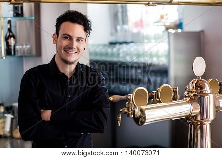 Portrait of young confident barkeeper standing at bar counter