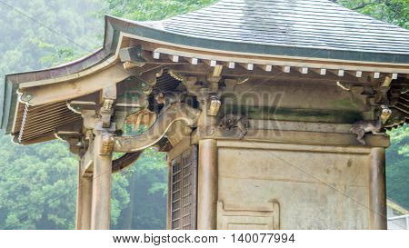 Japanese Macaque monkeys taking shelter under a small shrine from the rain in Japan.