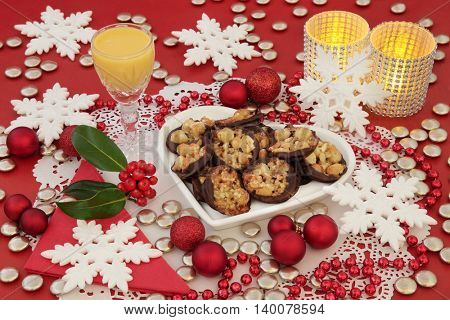 Christmas scene of florentine biscuits on a heart shaped plate, egg nog, holly, candles and bauble decorations with snowflakes on a red background.