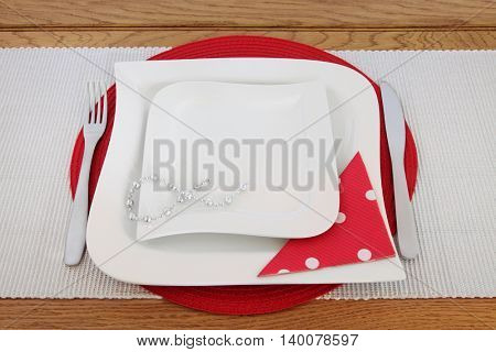 Elegant table setting with white porcelain plates, cutlery, decorative bead chain, polka dot serviette on red place mat and silver runner on oak background.