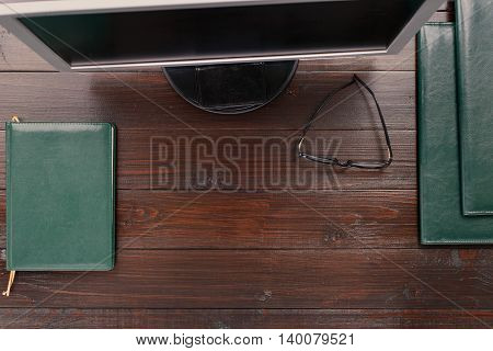 Office desktop with monitor leather folder notebook and glasses. Top view with copy space