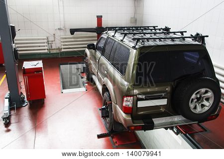 SUV on scheduled scanning at auto service. Professional car maintenance at modern repair shop