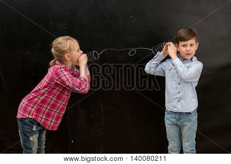 two funny shoolchildren talking on self-made drawn on the blackboard telephone